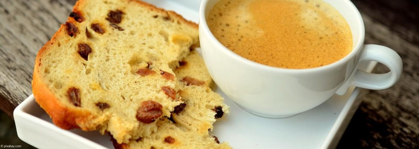 Tasse Kaffe mit einem angebissenen Stück Rosinenbrot