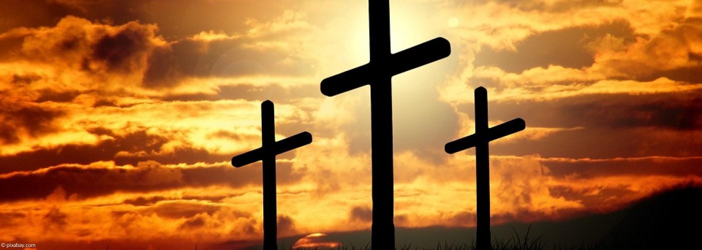 drei Kreuze, im Hintergrund ein Sonnenaufgang