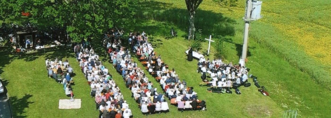 Luftbild von oben, Gottesdienst auf der Wiese, Altar, Bänke
