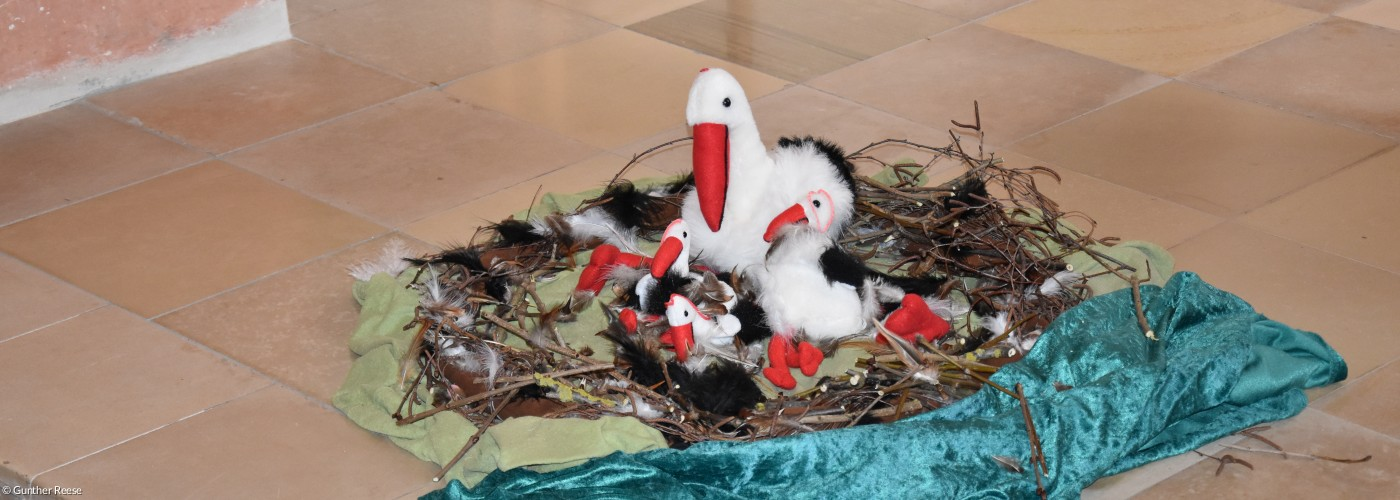 Storch aus plüsch in einem gebastelten Nest