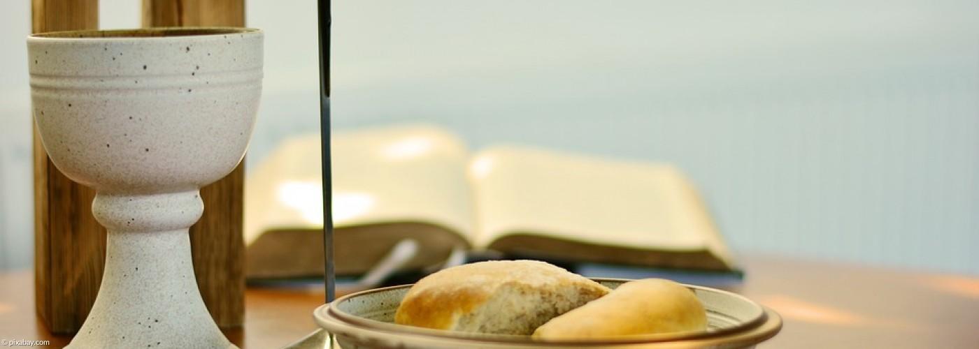 Weinkelch, Teller mit Brot, Kreuz und Bibel
